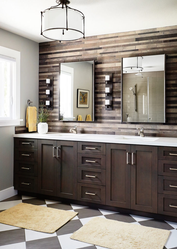 The bathroom boasts a breathtaking stone tile backsplash over the white countertop vanity, with black and white tile flooring below. More of the deep rustic wood tones appear on the drawers and cupboard doors in here.