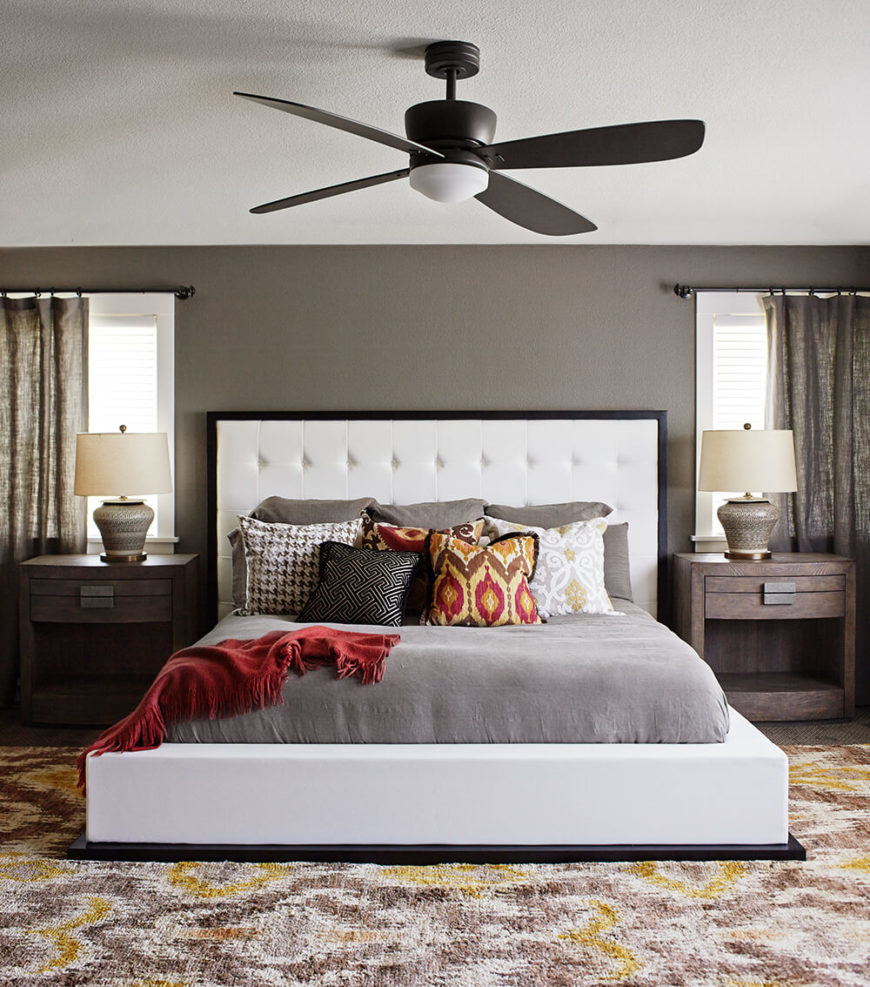 The master bedroom centers on a large platform bed frame with a matching white button tufted headboard. The bed is flanked by a pair of rustic wood side tables that are cut in a more modern fashion.