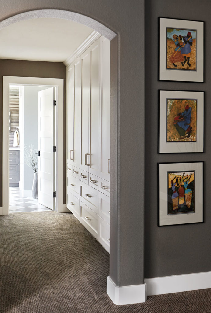 The master bedroom connects to the bathroom by way of an open closet space flush with storage options along the right wall. White cabinetry and drawers reach from floor to ceiling for the ultimate in discreet storage.