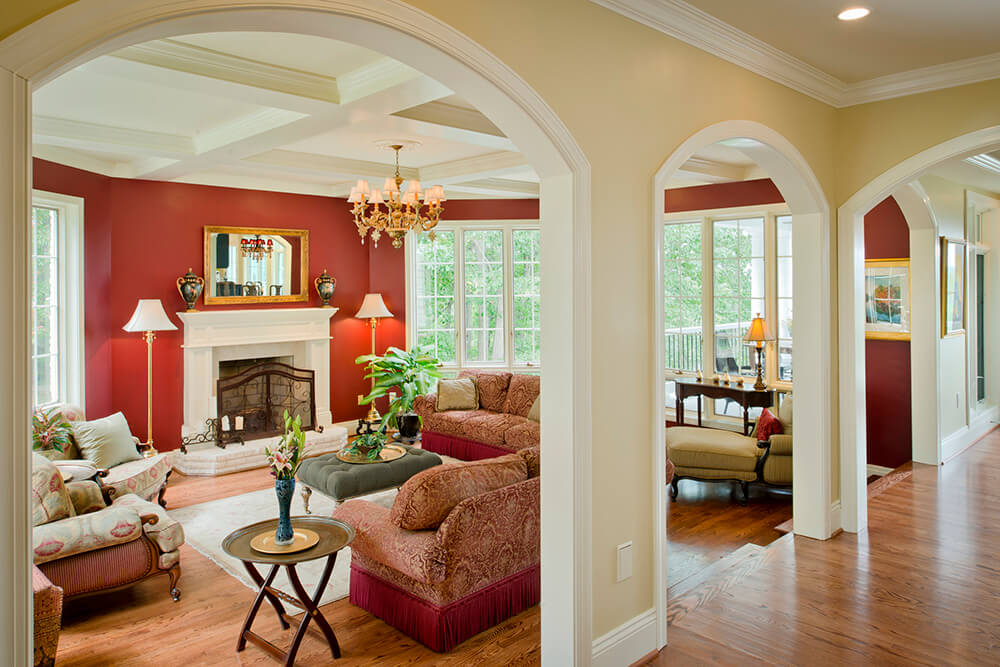 Large formal living room boasting red walls with white accent. The room also offers a cozy set of seats and a fireplace, lighted by a gorgeous chandelier hanging from the coffered ceiling.