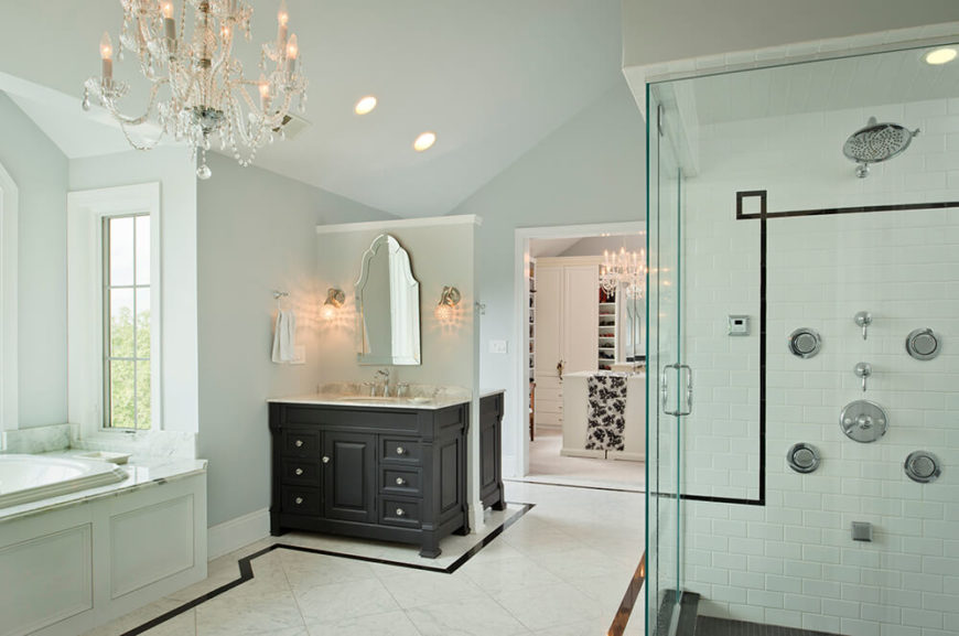 Dual vanities, one on either side of the partial wall, utilize the bathroom space well. Here you can also see the glass-walled walk-in shower that follows the simple black and white design of the room with shite subway tiling and a black tile floor. In the background you can see the walk-in closet attached to the bathroom.
