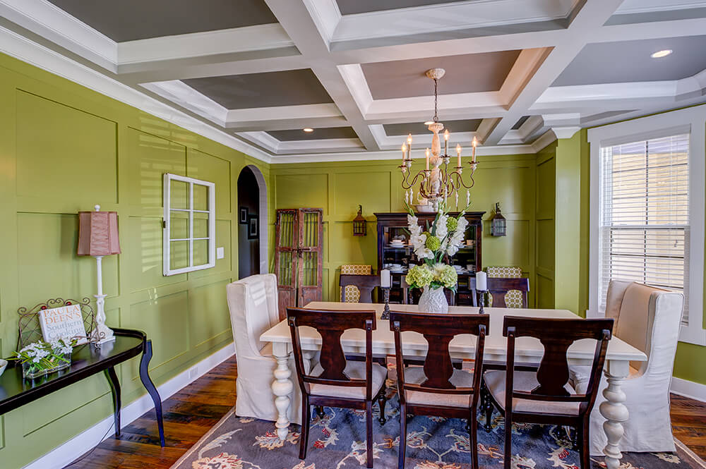 This dining room features green walls with a nice set of dining table lighted by a glamorous chandelier set on the room's coffered ceiling.