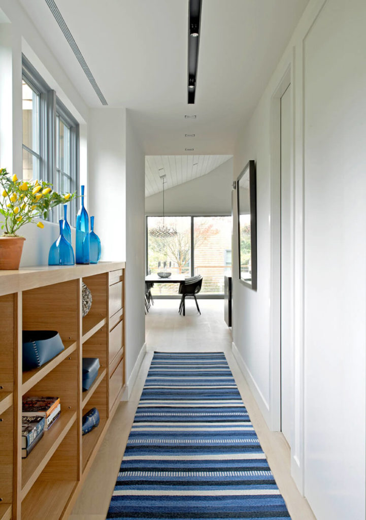 As you enter the Sagaponack Cottage, you'll turn to the right and immediately be greeted by this vibrant blue rug and naturally lit hallway. The white walls help the light bounce around, and the shelving and drawer space to the left provide plenty of area for storage, as well as providing a space for decoration.