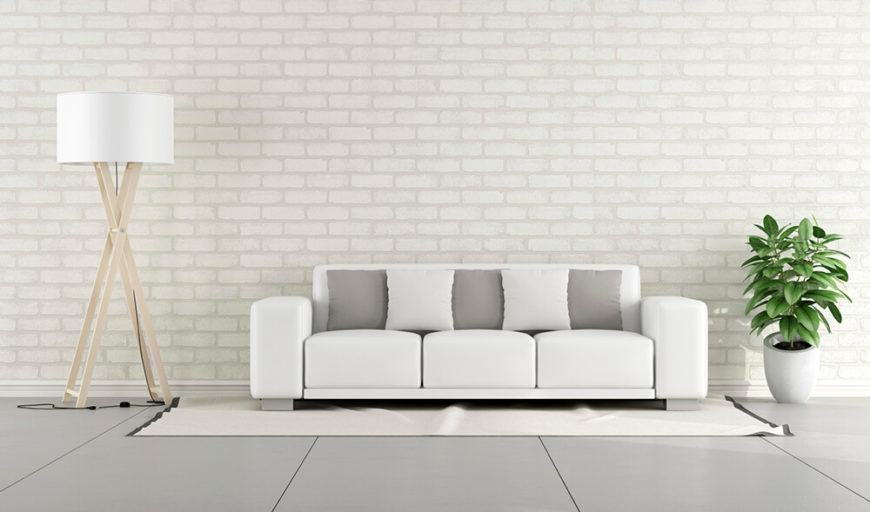 Likewise, brick can serve to complete a room's overall tone. The white brick in this living room helps propel the whites and grays in the furniture to peak effect. The white wall also accentuates the plant's vivid green color.