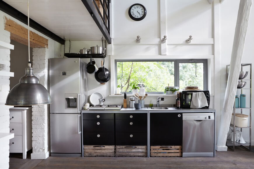As part of a much larger open space, the kitchen here is defined by its stainless steel appliances. A set of black cabinetry contrasts with white walls and rustic storage bins below.