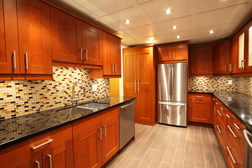 The Contemporary Shape Of The Rich Wood Cabinetry Meshes Perfectly With Stainless  Steel Appliances And A