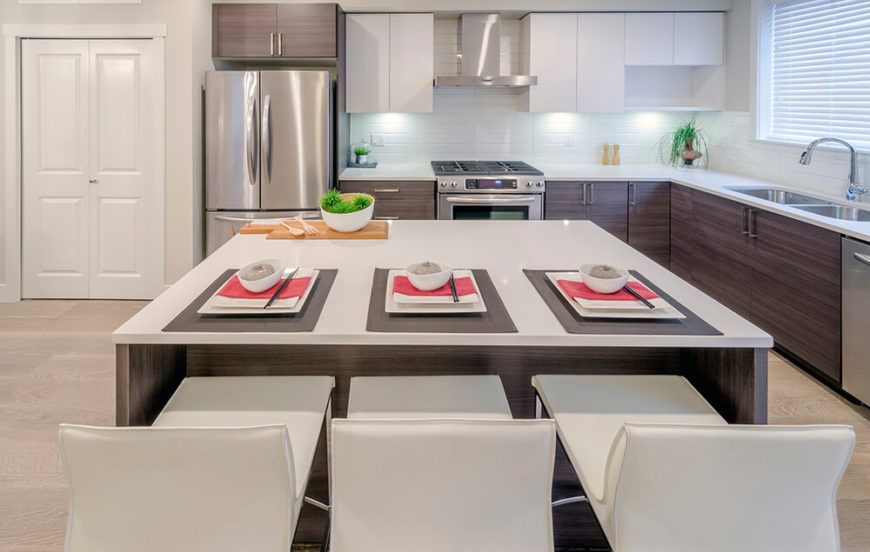Ultra modern minimalism informs this sleek kitchen, pairing white countertops, tile backsplash, and upper cabinets with rich wood lower cupboards and island. The stainless steel appliances add a small dose of contrast.
