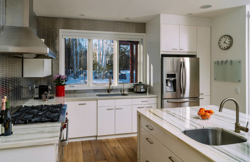 Sharp white cabinetry meets a micro-tile backsplash in this highly detailed, cozy kitchen. The island is wrapped in smooth marble, contrasting with the rustic hardwood flooring. Stainless steel appliances add yet another layer of contrast, making for a surprisingly cohesive whole.