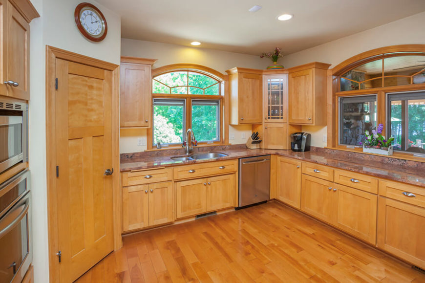 Warm light wood cabinetry matches the hardwood flooring in this large, open plan kitchen, contrasting with white walls and a blushing granite countertop. The subtle appearance of stainless steel appliances grants a bit of variety to the space without hogging visual attention.