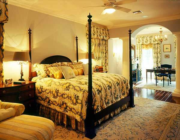 This bedroom features a bed with high bed posts and a headboard. The bed sits on a large area rug, which is resting above a rich hardwood floor. The room is well lit by lamps and other artificial lighting. On the far side of the room, there is a desk and office space, with a small fireplace to light for when working late into the night.