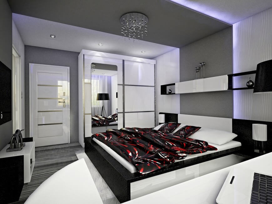 This bedroom has a prevalent black and white color scheme, accented only by the bedding and led perimeter lighting behind the bed. Sleek surfaces are also prevalent in this room, giving it a very modern feel. Although the room is spacious, the large bed takes up a lot of the room, while the desk area seems to occupy the rest of the otherwise free space.