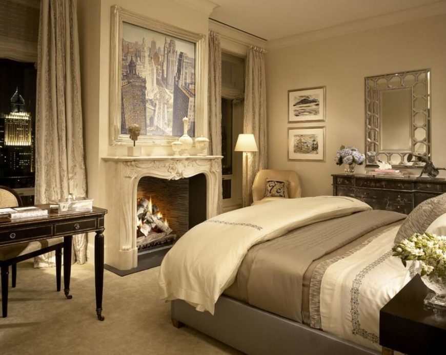 This bedroom has a spectacular view of the city from the windows, with a large fireplace set in between them. Regal themes and light beige colors help to make the space look sophisticated. A set of drawers sits beyond the bed with a large mirror above, while on the other side a desk is set facing away from the window.