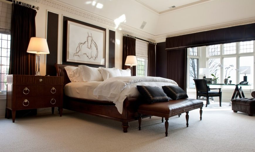 This large bedroom has plenty of space around the bed, with a high vaulted ceiling. The furniture is made up of rich stained wood and dark leather, suggesting a wealthy status. The light carpet and walls helps to contrast the darker furniture, while the large windows provide plenty of natural light for the desk space. Curtains are featured to help separate the work space from the bedroom.