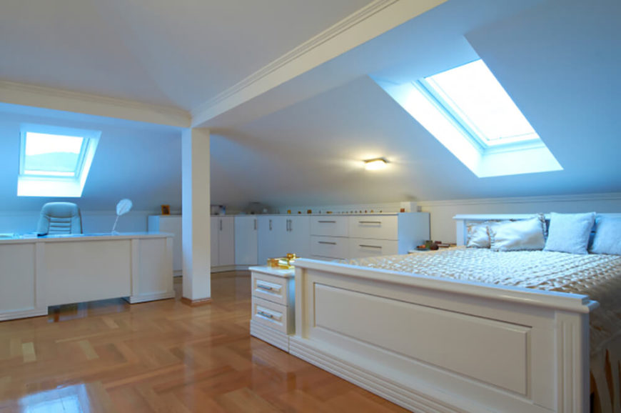 This bedroom is sleek and modern, with clean white walls and furnishings. The slanted ceiling suggests this bedroom is located near the top of the house, and the skylights let natural light flood in, illuminating the bed and desk areas. There is a unique pattern on the hardwood floor, with a high gloss to help reflect light.