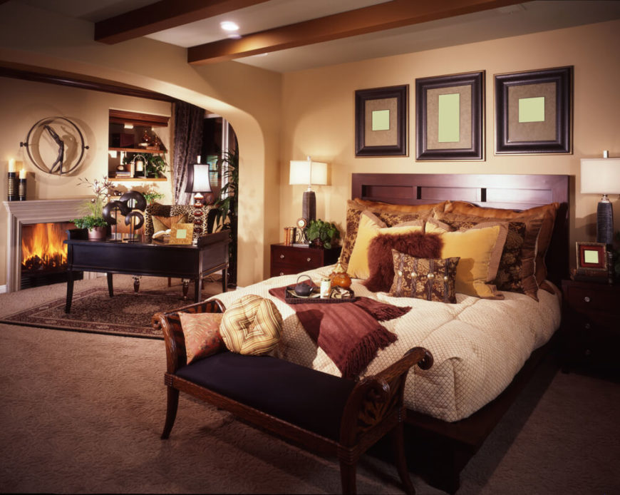 This bedroom is a sophisticated space with rich wood finishings and deep, dark colors. The bed is covered in stuffed pillows and blankets, while to the left a desk is featured. Next to the desk you will notice the small fireplace, with candles and decorations above the mantle. Shelving units directly next to that provide a space for storage, as well as for more decoration.