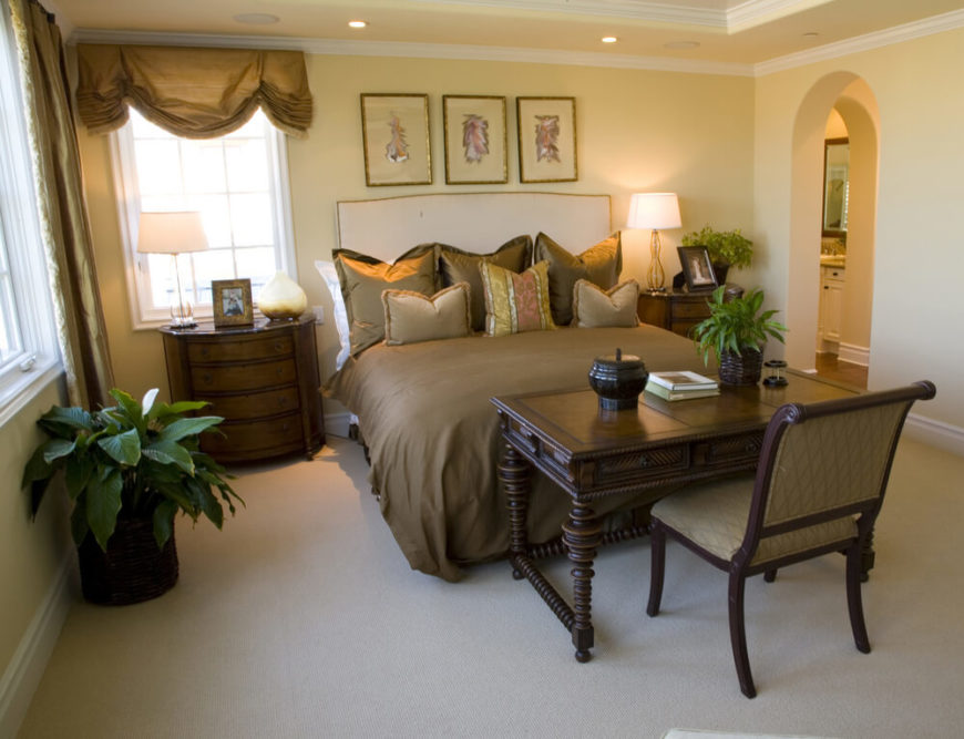 Unlike many of these bedrooms, this space has a desk set directly at the foot of the bed, so that you will be facing the bed as you are sitting at the desk. Rich wood makes up the desk as well as the bedside tables, and the green foliage helps to accent the dark colors in the room.