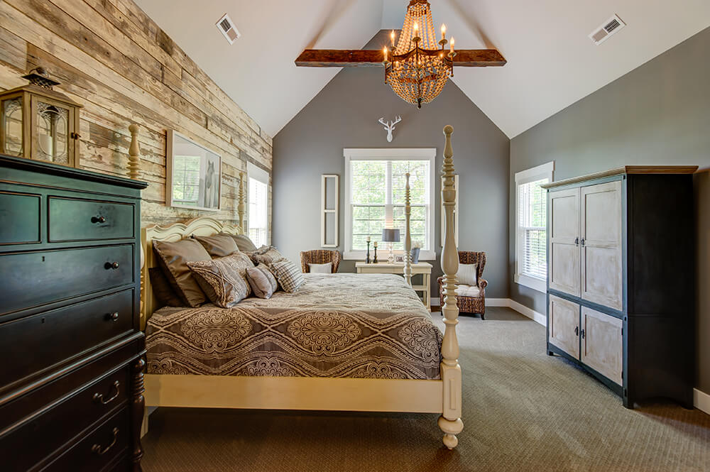 A very attractive master bedroom featuring gray walls and vaulted ceiling lighted by a glamorous chandelier.
