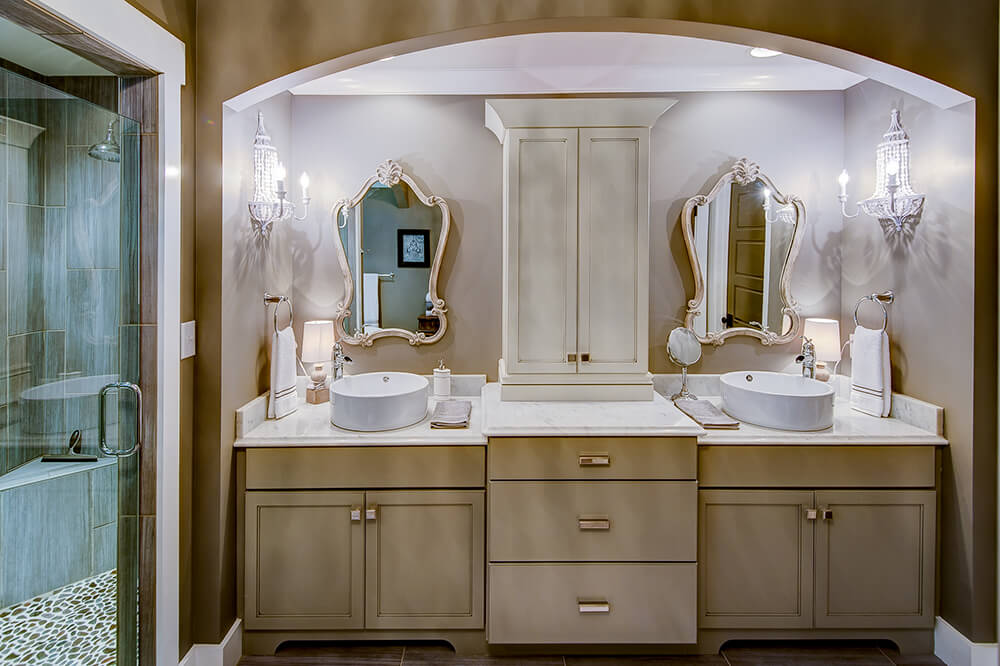 This master bathroom offers a lovely bathroom counter area with two sinks and a glamorous set of mirrors and lights. There are a freestanding tub and a walk-in shower area in the corner.