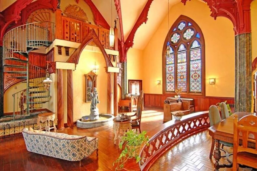 This massive space appears to be a conversion from a former church. The high vaulted ceilings and intricate design on the trim work together to create a specific atmosphere. The large stained glass window lets in natural light, and also provides a bright variation of color from the rest of the room.