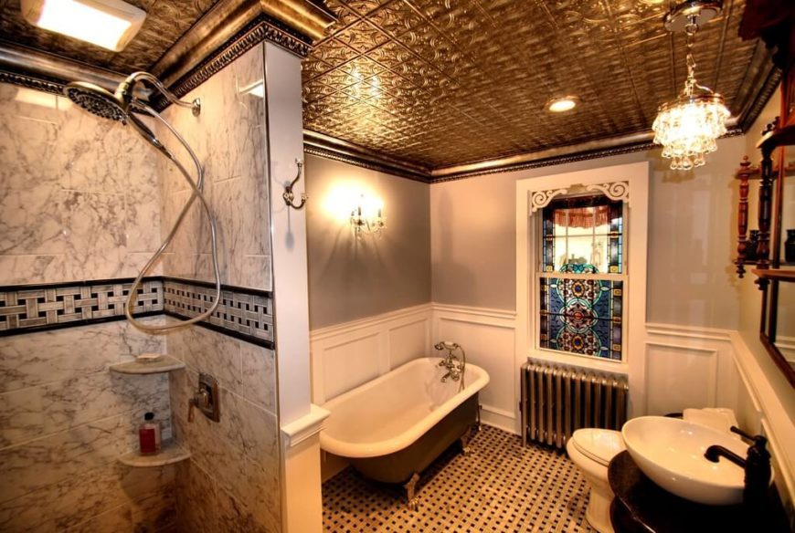 This bathroom is well lit by natural light. A woven pattern covers the floor, and the ceiling is covered with tin tiles. The window is covered with stained glass, which almost disguises it to make it look less like a window and more like a design feature.