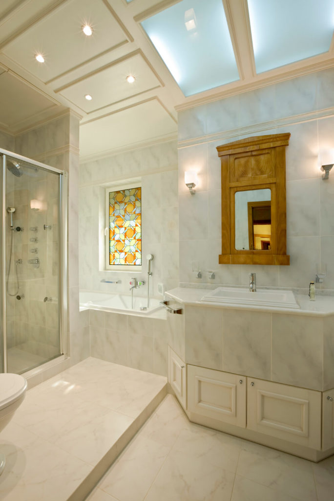 This bathroom is covered in white marble tile, with white cabinet doors and trim. The bath is tucked into the corner behind the shower, and directly above the bath is a colorful section of stained glass, contrasting the otherwise solely white space.