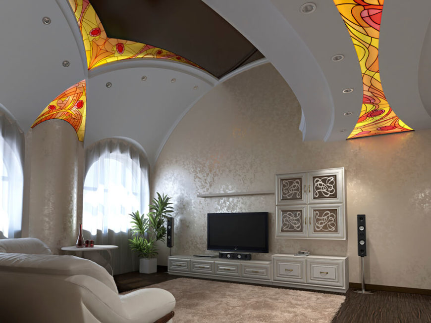 This is a large living room with high vaulted ceilings. There is an entertainment center with white cabinetry for storage, and a large plush rug before it for comfort. Stained glass sections are incorporated into the ceiling.