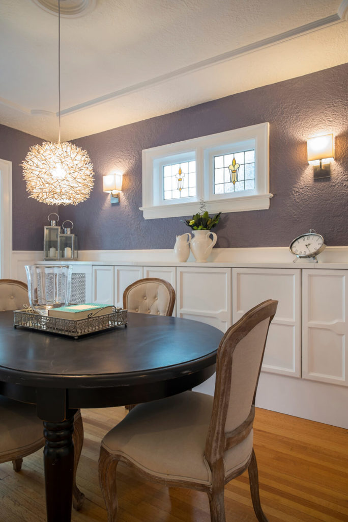 This dining room has s row of white cabinets along the bottom half of the wall, with a deep purple paint covering the top half. Stained glass windows provide a touch of elegance for the space.