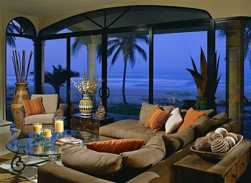 Floor to ceiling windows accompany a glass sliding door, giving this living room a wide view of the beach front. Intricate patterns on the decor give the space character, while furniture surrounding a glass coffee table provide optimum comfort.