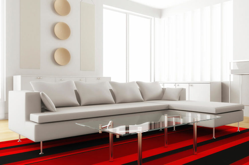 This Living Room Features A White Couch With Sharp Right Angles. The Chrome  Silver Table