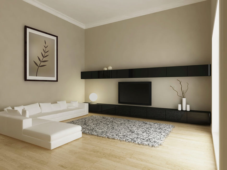 This living room is minimal, yet extremely spacious. The hardwood floors are a light wood grain, illuminated by natural light from the windows. A plush rug provides a comfortable surface, while the large L-shaped couch helps to frame the room.