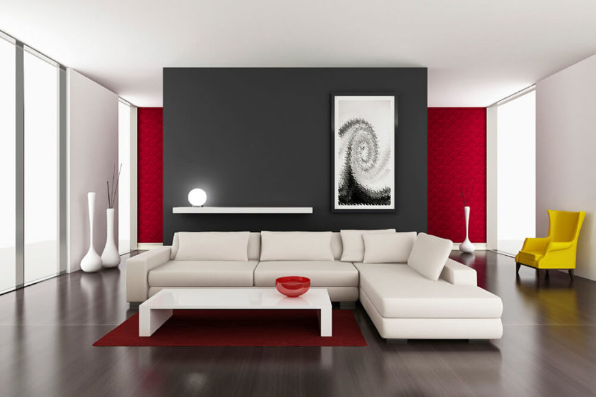 A modern design, featuring a high contrast of color. The white sofa sits upon a dark stained material floor, while the black accent wall contrasts the surrounding white walls and the ceiling. The crisp surfaces contribute to the modern atmosphere.