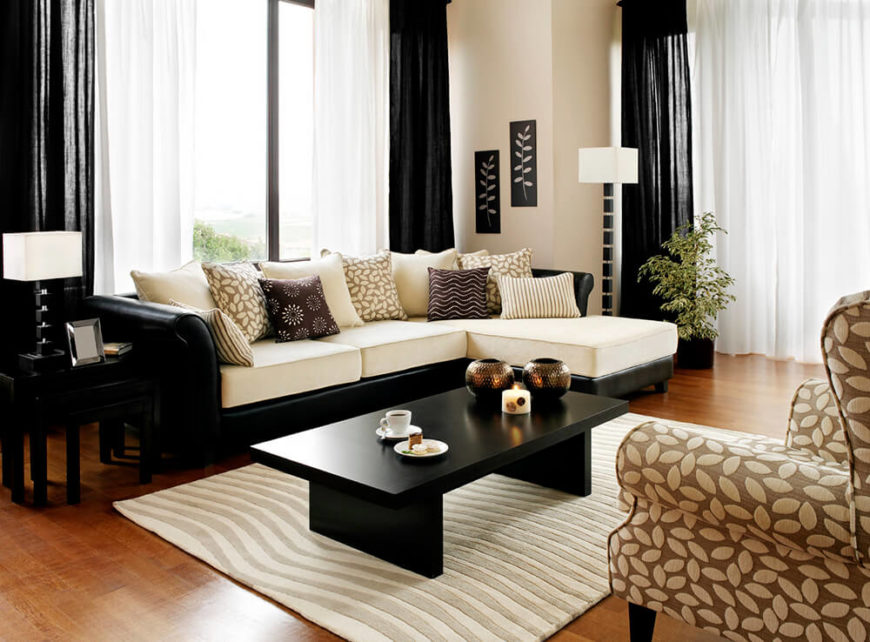 The sleek coffee table is pitch black, heavily contrasting the area rug and the white couch cushions. The black and white theme is continued with black curtains framing the white in between.
