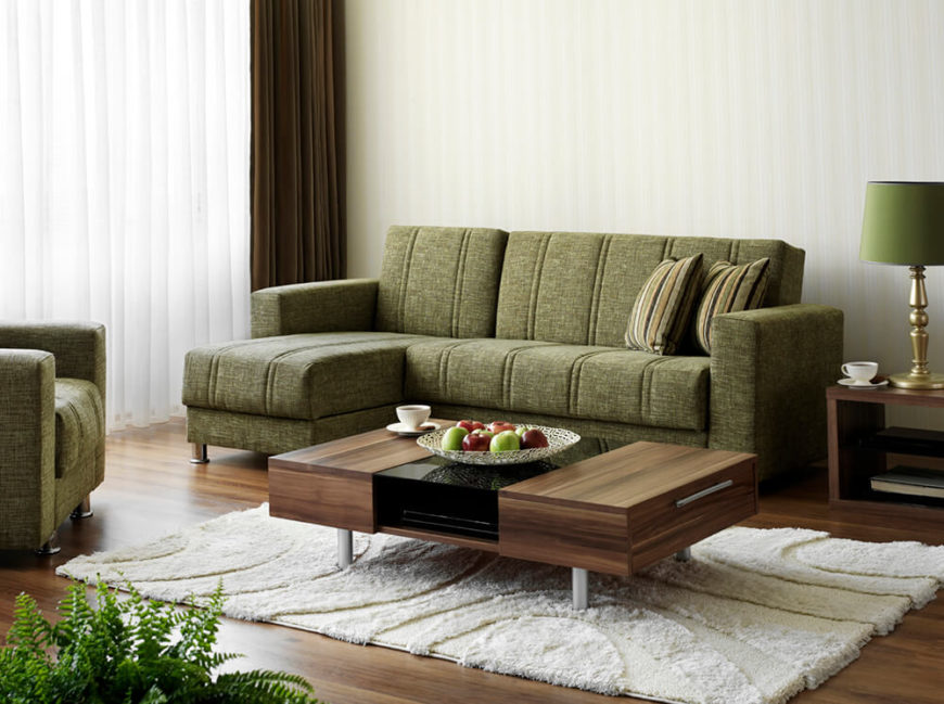 Stained hardwood for the flooring matches that of the coffee table and side tables. The plush white rug heavily contrasts the darker colors, and the green couch and lampshade balance the space. A large window lights the room with natural light.