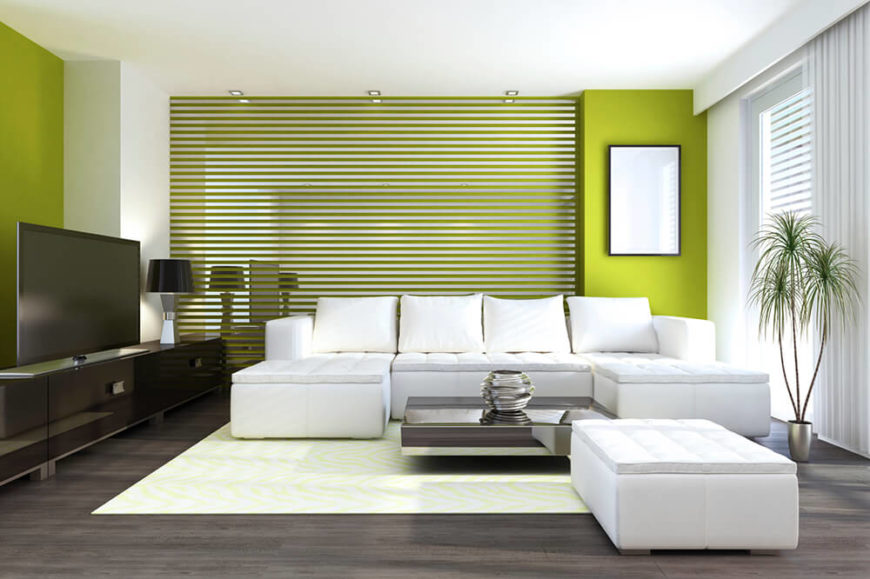 This living area has a fine balance of color. The white sofa wraps around a sleek reflective coffee table. There is a black stained hardwood floor beneath a key lime carpet. The green walls are complimented by the decorative plant.