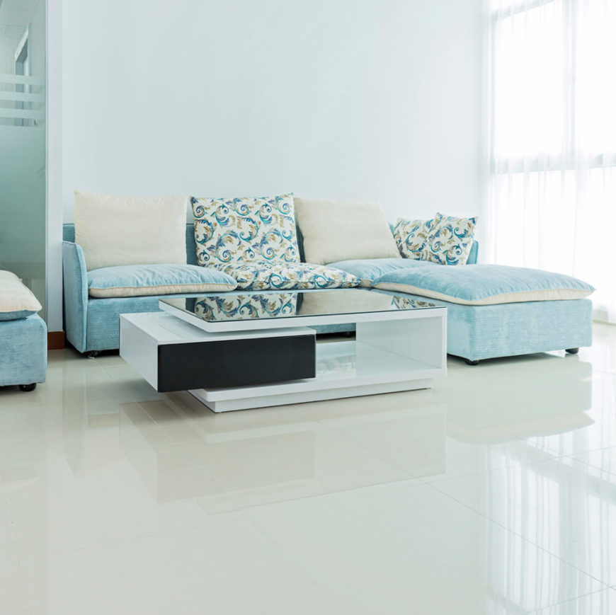 The high gloss white floor reflects the natural light from the windows, making this living room bright and airy. The sky blue sofa sits just behind a unique coffee table, which also has a sleek finish.