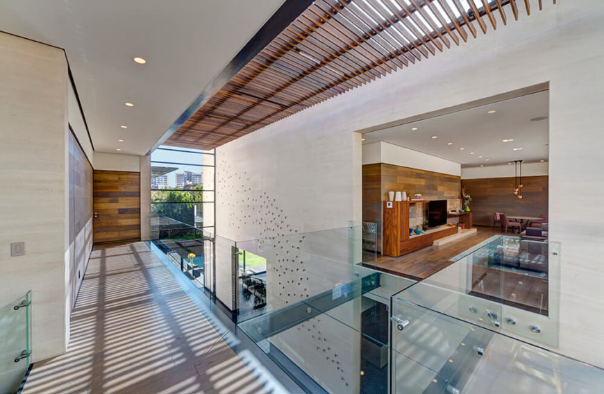 Wooden louvered panels above diffuse direct sunlight throughout the open lobby space, supplanted by full height glazing on both ends. To the right, a cozy living room space is seen defined by rich wood paneling.