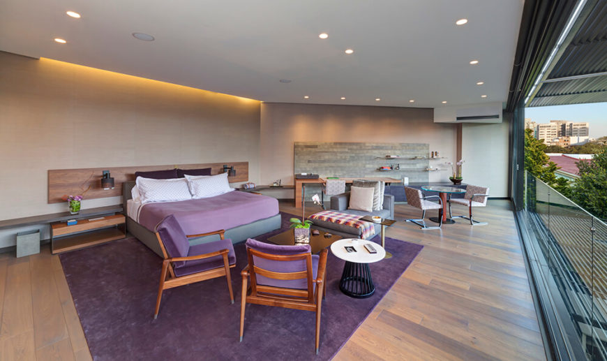 The master bedroom is an expansive space, combining both the beige tone of limestone and the warm wood textures seen in the nearby family room. Bursts of purple appear courtesy of a large area rug, chairs, and bedding. This entire space overlooks the backyard landscape, sheltered by shade louvers.
