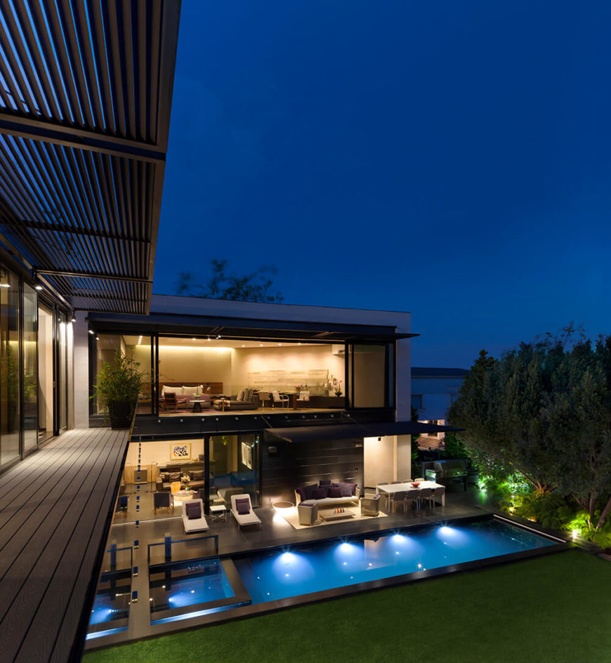 From a lengthy second floor balcony, we can see the radically open design of the home through full height windows and sliding glass panels that blur the line between interior and exterior spaces.