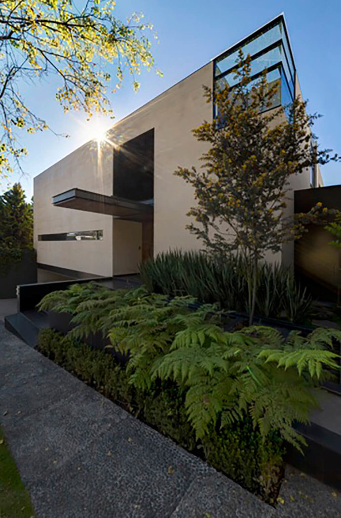 The front entry stands beneath an extended shade, a welcoming but private design choice that barely hints at the spectacular home within.