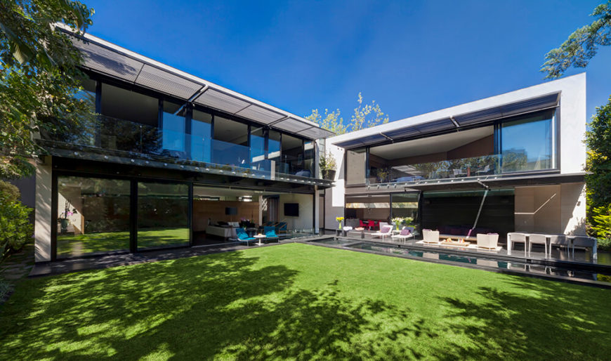 From across the yard, we can see the twin volumes of the home, joined at the center by the lobby structure. While the exteriors match, the interiors of each half of the home serve very different purposes.
