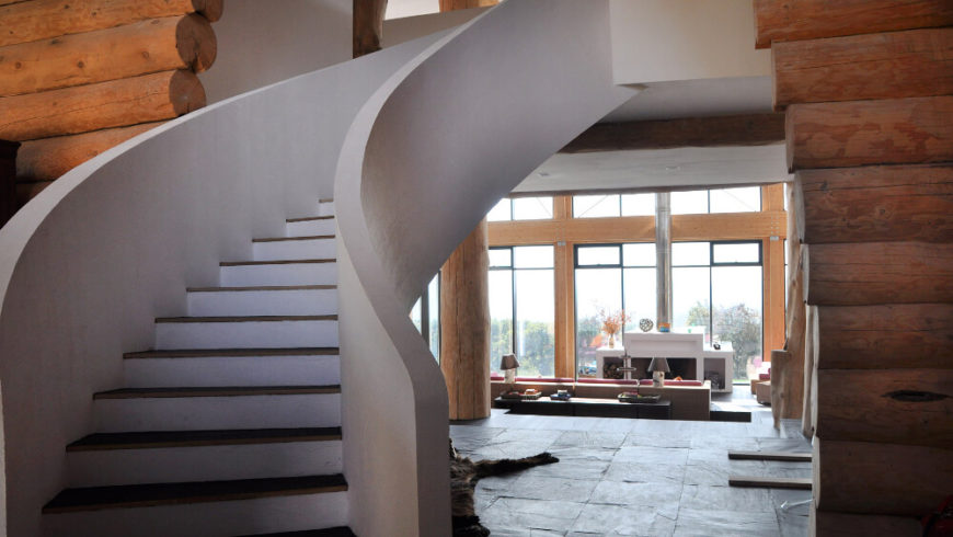 A curved staircase floats out over the open space in white, defining the look of the upper floor as distinct from the earthy first floor. Beyond, we see the living room sprawling beneath a set of massive windows.