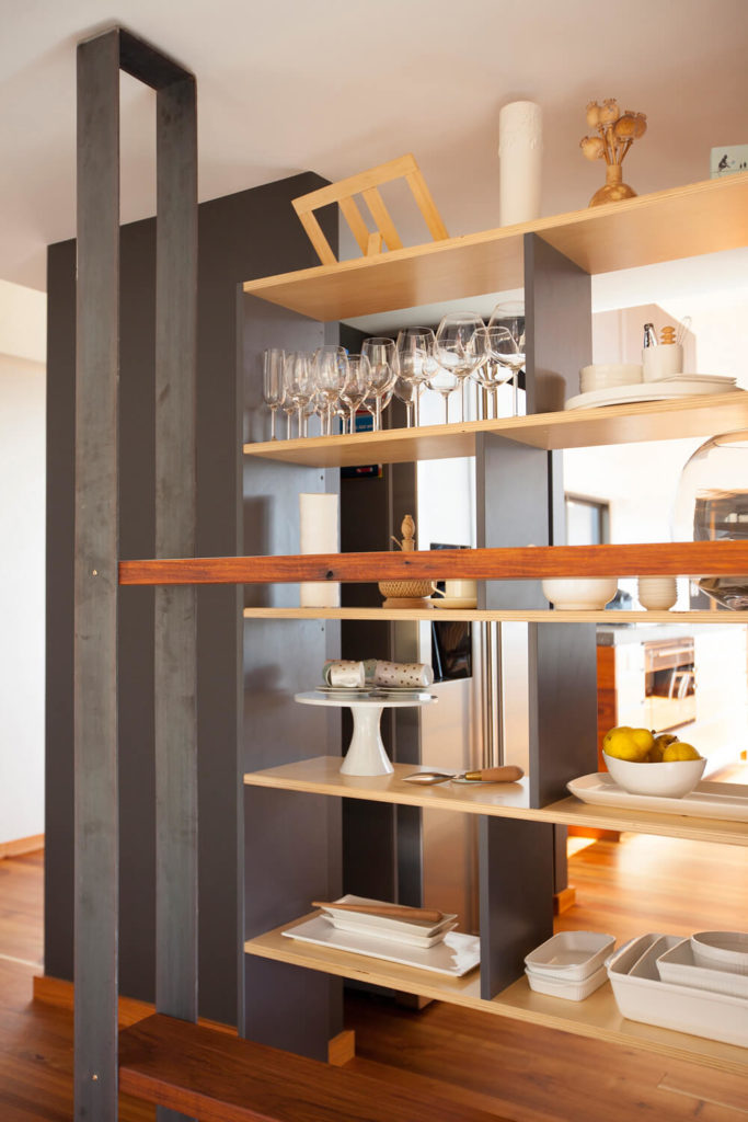 This close up view of the shelving unit shows how the dishes and serving utensils can be accessible from both the living room and the kitchen. The combinations of the dark painted wood and the lighter tones is well executed.