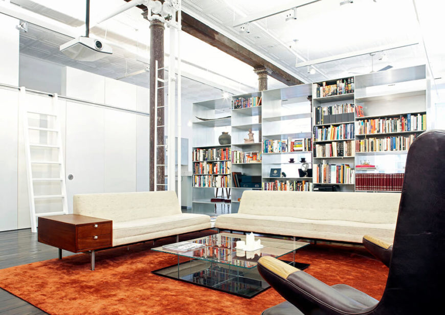 The study takes up the center portion of the house and serves as the study and entertainment room. The burnt orange silk rug was also custom designed — like its blue counterpart in the living room. The backside of the metal shelving has been divided into smaller, shallower shelves to hold books and other personal decorations.
