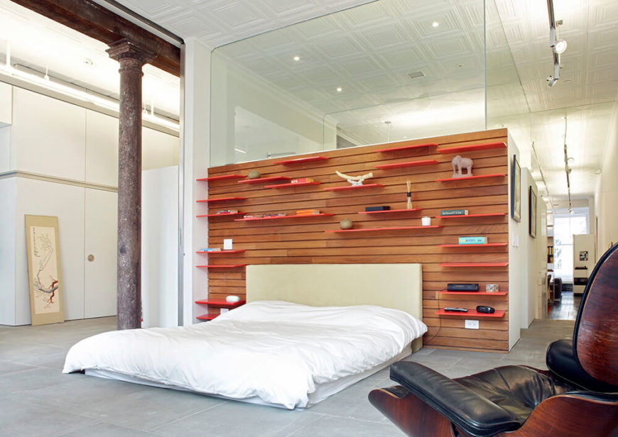 The master bedroom is the final area of the house, taking up the entire west end of the apartment. The accent wall behind the bed is covered in teak slat wall; bright orange shelves have been inserted into the wall and can be moved as the owner sees fit. The accent wall shares a wall with the master bathroom.