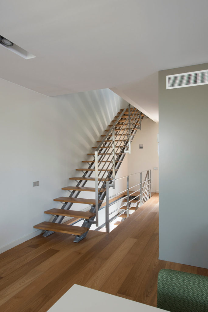 The stair case of the home is consistent with the rest of the flooring. The actual steps are made of the same rich wood material, the railings and the frame are stainless steel metal.
