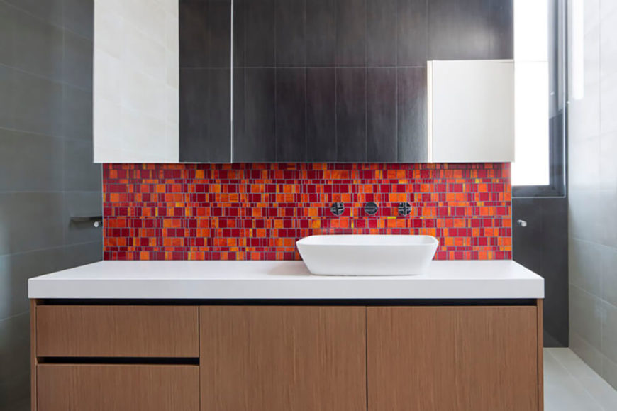Each of the four bathrooms are a study in brilliant color. With similar mosaic tiles unifying all of the spaces, the rest of the bathroom designs are wonderfully sleek and minimal, with muted hues, so as to highlight this use of color. This bathroom features a fiery red/orange combination of tiles to warm up the space.