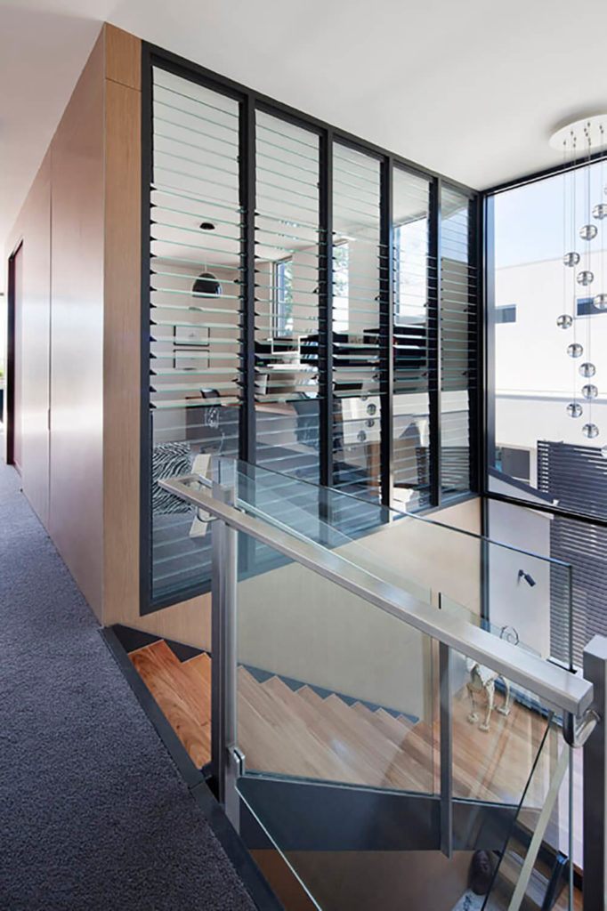 """The study was one of the necessary additions that the owners requested be worked into the design of the second floor extension. Rotating glass """"blinds"""" allow the space to be open or allow for privacy without blocking any of the natural light afforded by the many windows."""