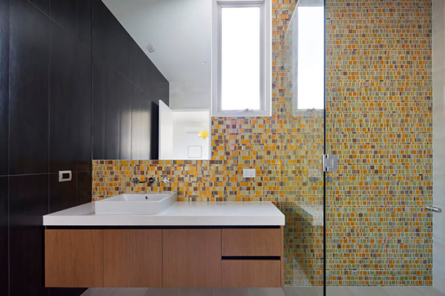 Featuring similar but slightly different vanities and sink combinations, the designs of the bathroom help to tie them all together. A glass walled shower in this bathroom allows you to see the full effect of the yellow tile design while the sharp edges of the mirror and window break up the space in a creative way.