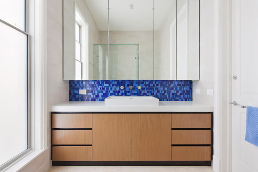 The small pop of blue in this bathroom is just enough to create visual interest and break up the use of white throughout the surfaces. A large mirror reflects light and offers extra storage in the room with shelving behind it. Natural wood also helps to break up the bright space.