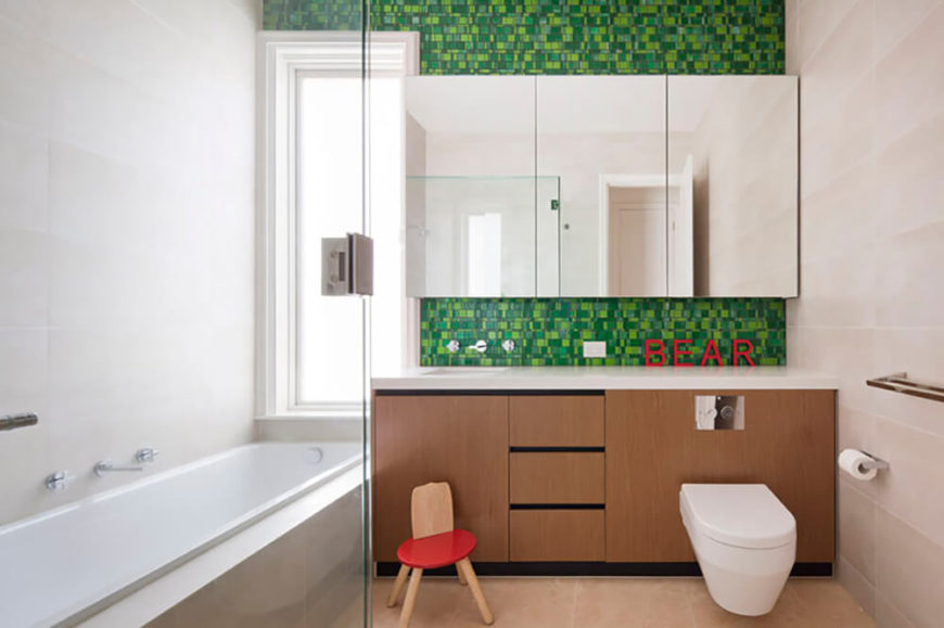 Green tiles make up the accent wall in this room, with little splash of red introduced into the design. Pale hues and natural wood continues the theme from the rest of the bathrooms while a full-size soaking tub has been introduced into this room for the kids.